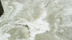 Rapid stream of muddy river beat about bridge column Stock Footage