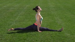 Flexible girl doing gymnastic exercises on the grass Stock Footage