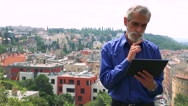 Old senior man works on tablet - city (buildings) in background Stock Footage