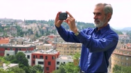 Old senior man takes photos wirh smartphone - city (buildings) in background Stock Footage