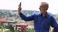 Old senior man photographs with smartphone (selfie) - city (buildings)  Stock Footage