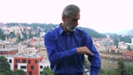 Old senior man adjusts clothes and smiles to camera - city (buildings)  Stock Footage