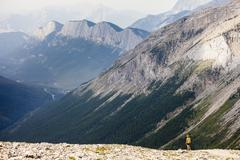 A young woman hikes the Sulphur Skyline Trail with a view of Ashlar Ridge. Stock Photos