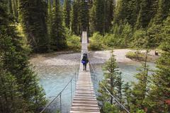 A back packer crosses a suspension bridge over a river in Kootenay National Stock Photos