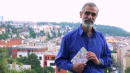 Old senior man holds book and smiles to camera - city (buildings) in background Stock Footage