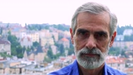 Old senior man looks to camera with serious face - city (buildings)in background Stock Footage