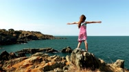 Little beautiful girl walks on a stone rocks Stock Footage