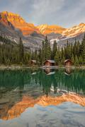 Lake O'Hara Lodge guest cabins are reflected in the calm lake at sunset. Lake Kuvituskuvat