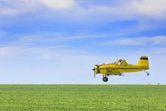 Crop duster airplane spraying farm field, Saskatchewan, Canada. Stock Photos