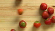 Many strawberry roll on a wooden surface. Slow Motion. Top View. Stock Footage