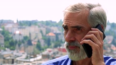Old senior man phones with smartphone - city (buildings) in background - closeup Stock Footage