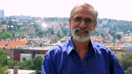 Old senior man smiles to camera with glasses - city (buildings) in background   Stock Footage