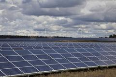 Large solar farm with windmills in background in southwestern Ontario (near Lake Stock Photos