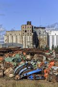 Scrap metal recycling, with an abandoned grain elevator in background, Thunder Kuvituskuvat