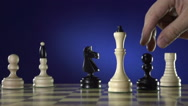 Black chess player knocks down the white king with his piece Stock Footage