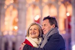 Senior couple walking in night city. Winter, Historical building Stock Photos