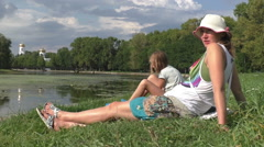 Mother and dauther sitting on the meadow in the park Stock Footage