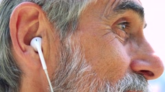 Old senior man listens music with earphone on smartphone - closeup Stock Footage