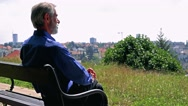 Old senior man sits on the bench in the park and looks at the city  Stock Footage