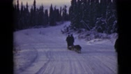 1946: men walking in the snow with sledge dogs pulling luggage ALASKA Stock Footage