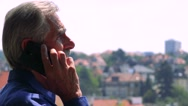Old senior man sits on the bench in the park and phones with smartphone - city  Stock Footage