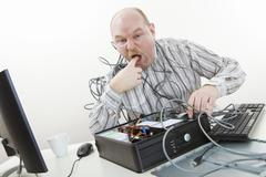 Irritated Businessman Licking Finger While Repairing Computer Stock Photos