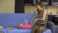 Mother tickle and hug baby daughter on blue sofa at home Stock Footage