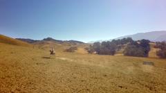 Cowboy on horseback on mountain range on sunny day slow motion 4 Stock Footage