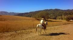 Cowboy on horseback traveling on mountain range on sunny day slow motion 6 Stock Footage