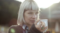Woman having a cup of tea outdoors Stock Footage