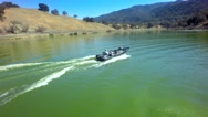 Drone view of motorboat traveling across a lake by mountains Stock Footage