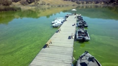 Aerial view of lakeside dock and boats by mountainside on a sunny day 5 Stock Footage
