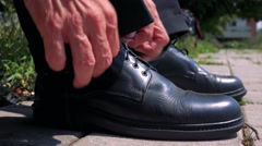 Old senior man ties up leather shoes in the park - detail  Stock Footage