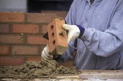 Construction work. Bricklayer applies mortar while constructing brick wall, Stock Photos