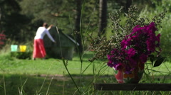 Young woman draws up water in a bucket from a well Stock Footage