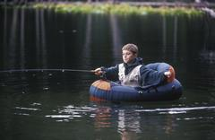 Boy fly fishing from float tube in small lake, British Columbia, Canada. Stock Photos
