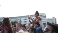 Kid girl sit on father shoulders in concert people crowd shoot video via phone Stock Footage