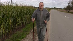 Hiker with walking sticks near corn field Stock Footage