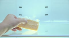 The man takes out of an empty refrigerator last piece of hard cheese Stock Footage