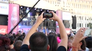 Fan guy in people concert crowd shoot phone video above heads Stock Footage