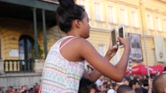Teenager girl shoot smart phone video sit on father shoulders during concert  Stock Footage