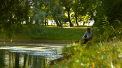 Lonely grandfather sits on the lake in the summer park Stock Footage