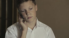 Close-up portrait of a schoolboy talking over telephone Arkistovideo