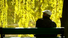 Lonely man (grandfather) is sitting on a bench in the park, rear view Stock Footage