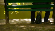 Lonely man (grandfather) is sitting on a bench on the shore of the pond Stock Footage