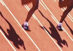 Two sprinter's legs running side by side on a track, British Columbia, Canada. Stock Photos