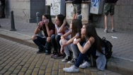 Teenager girls friends company sitting on the curb communicate on public street Stock Footage
