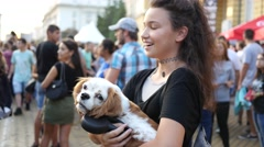 Cute teenager girl stay with dog in hands in crowd of concert people outdoors Stock Footage