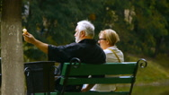 Elderly couple cute about something talking, sitting on a bench in the park Stock Footage