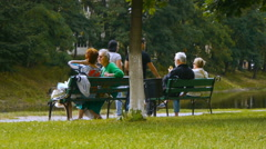 Elderly people sit in the park on the benches by the pond and talking, side view Stock Footage